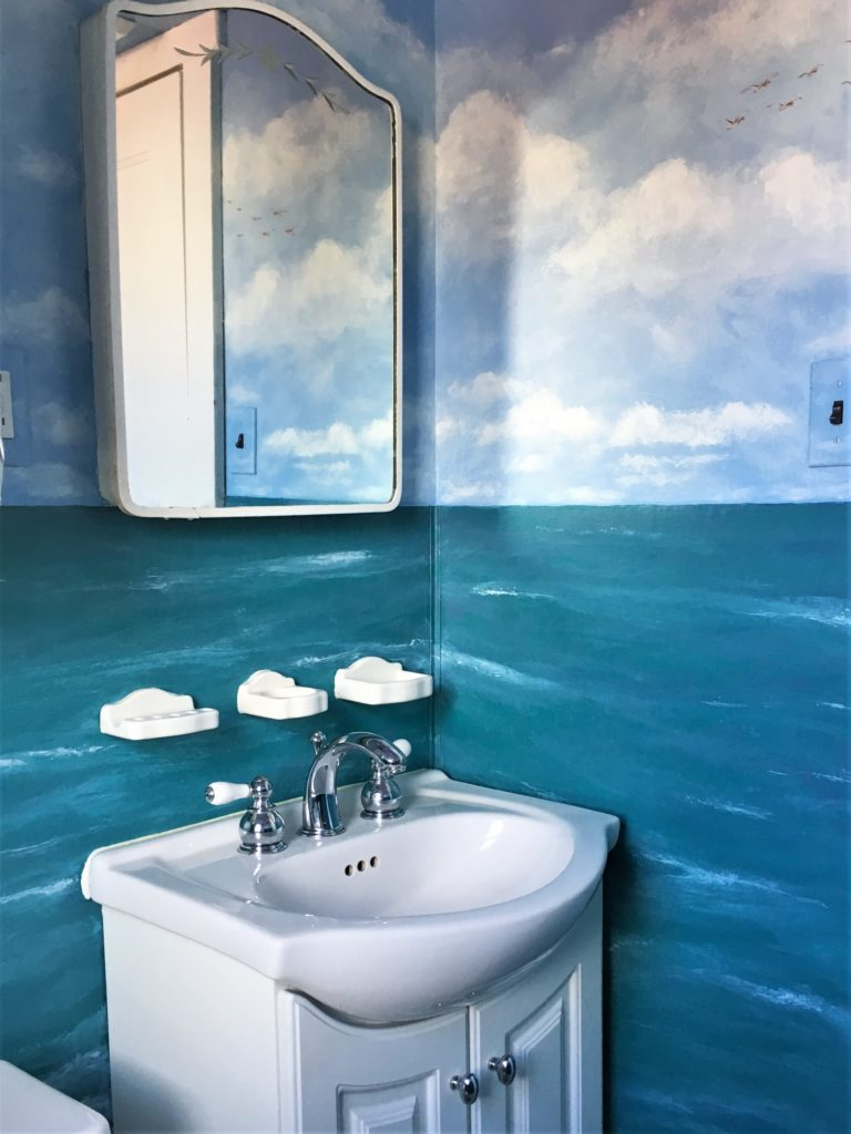 Small powder room painted with sky and ocean mural.