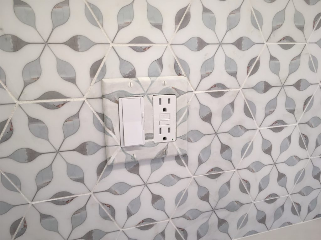 Switch/outlet cover-plates painted to match the design of the marble tile, and blend into the backsplash composition.