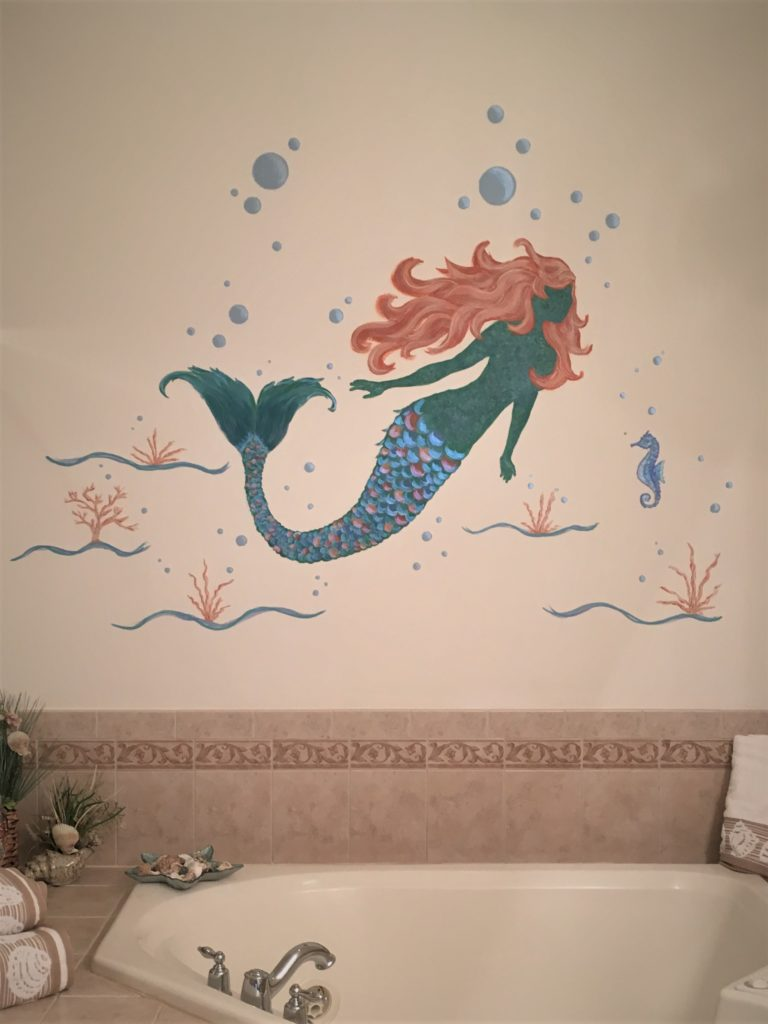 Mermaid mural with seahorse and bubbles painted in bathroom.