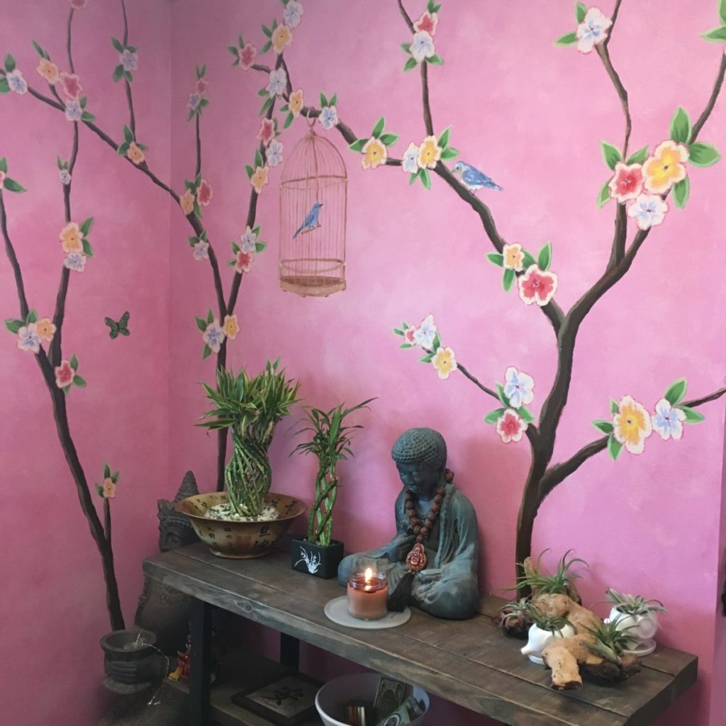 Foyer painted with tropical flowers, branches, birds and butterflies over a blended pink background.