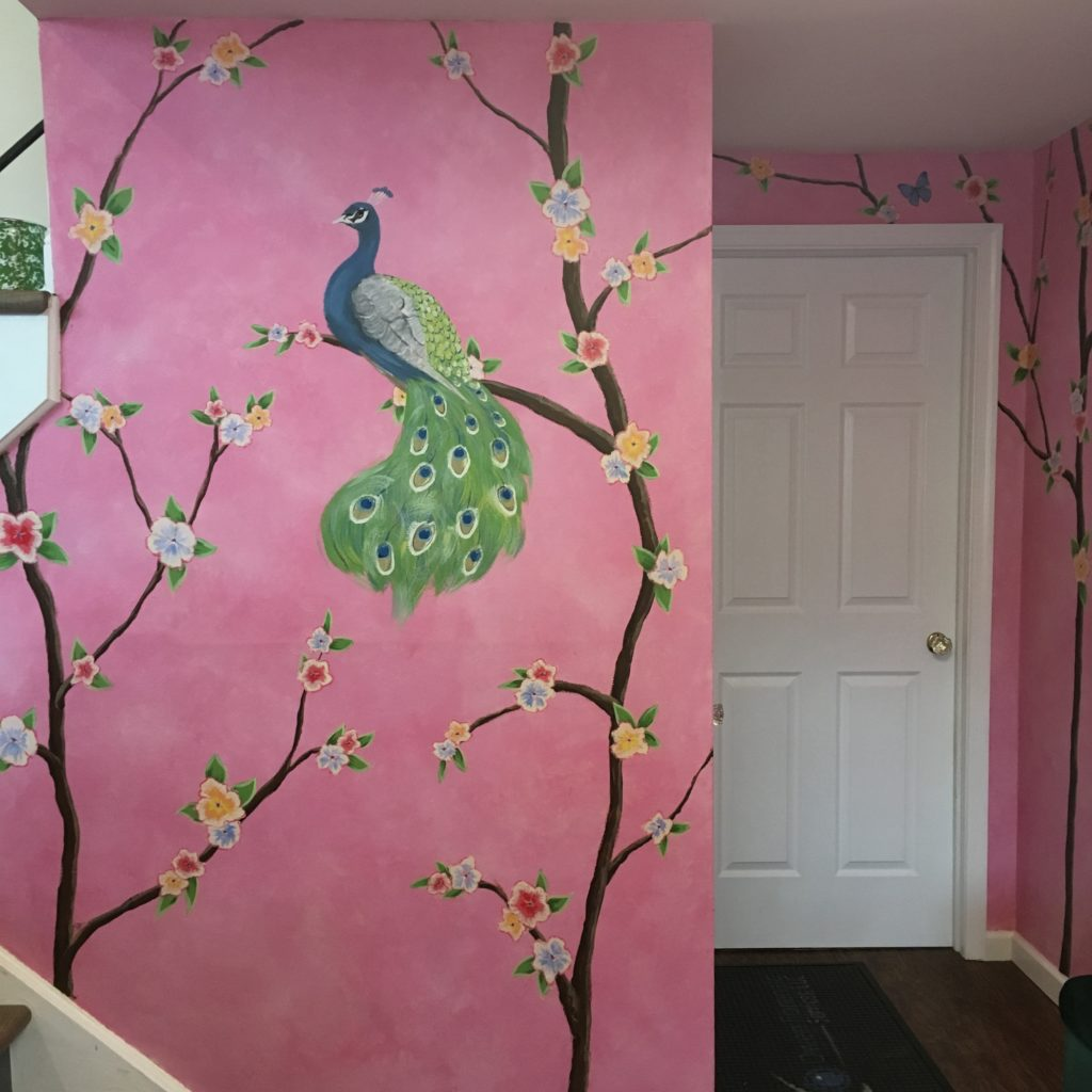 Foyer painted with peacock, tropical flowers, branches, birds and butterflies over a blended pink background.