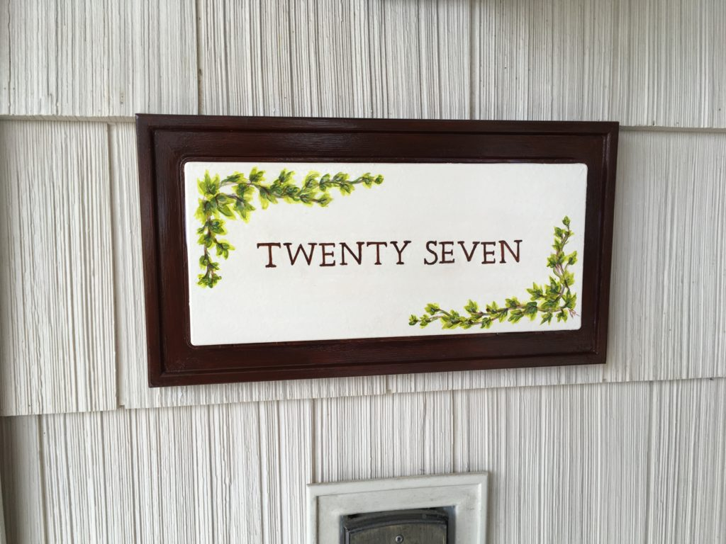 Address plaque painted on existing backlit plastic unit, including ivy and hand lettering