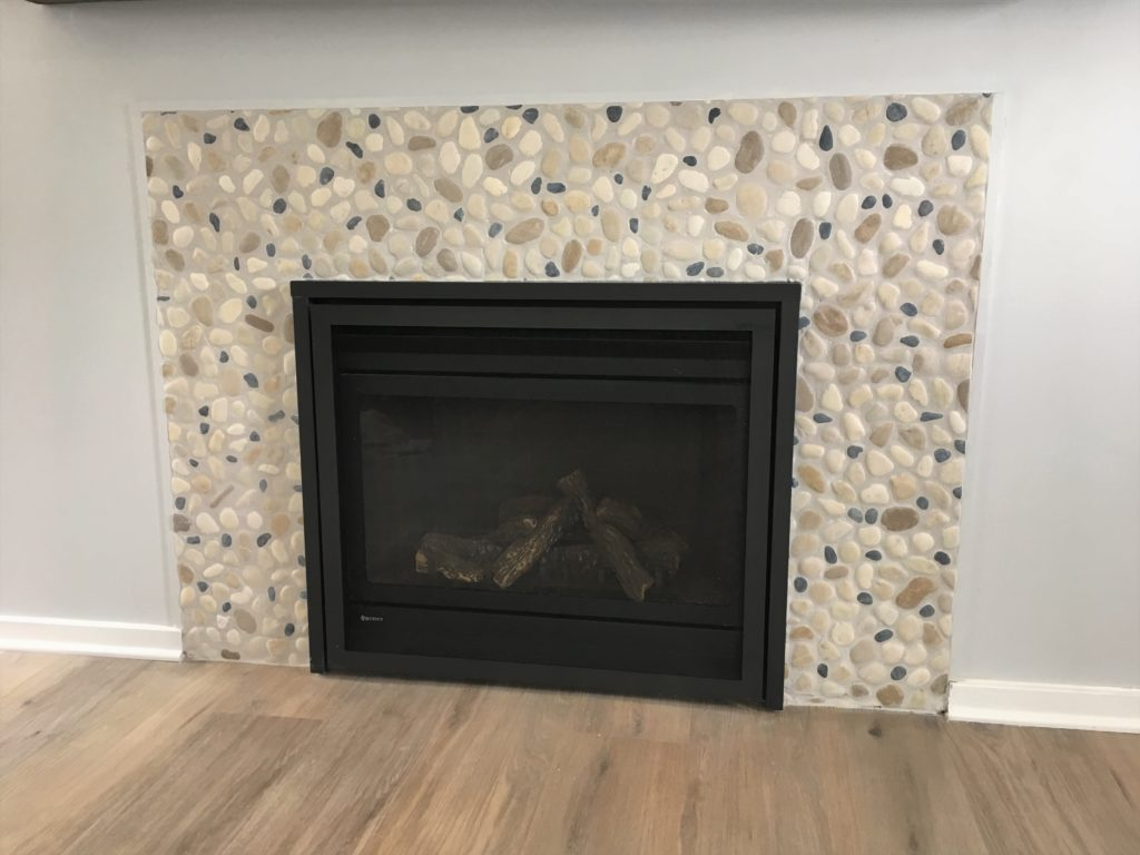 Natural pebble stone fireplace surround, painted with a grey wash to tone down the colors