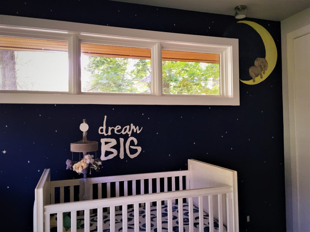 "Nursery mural accent wall with stars, ""dream big"" quote, and baby animals."