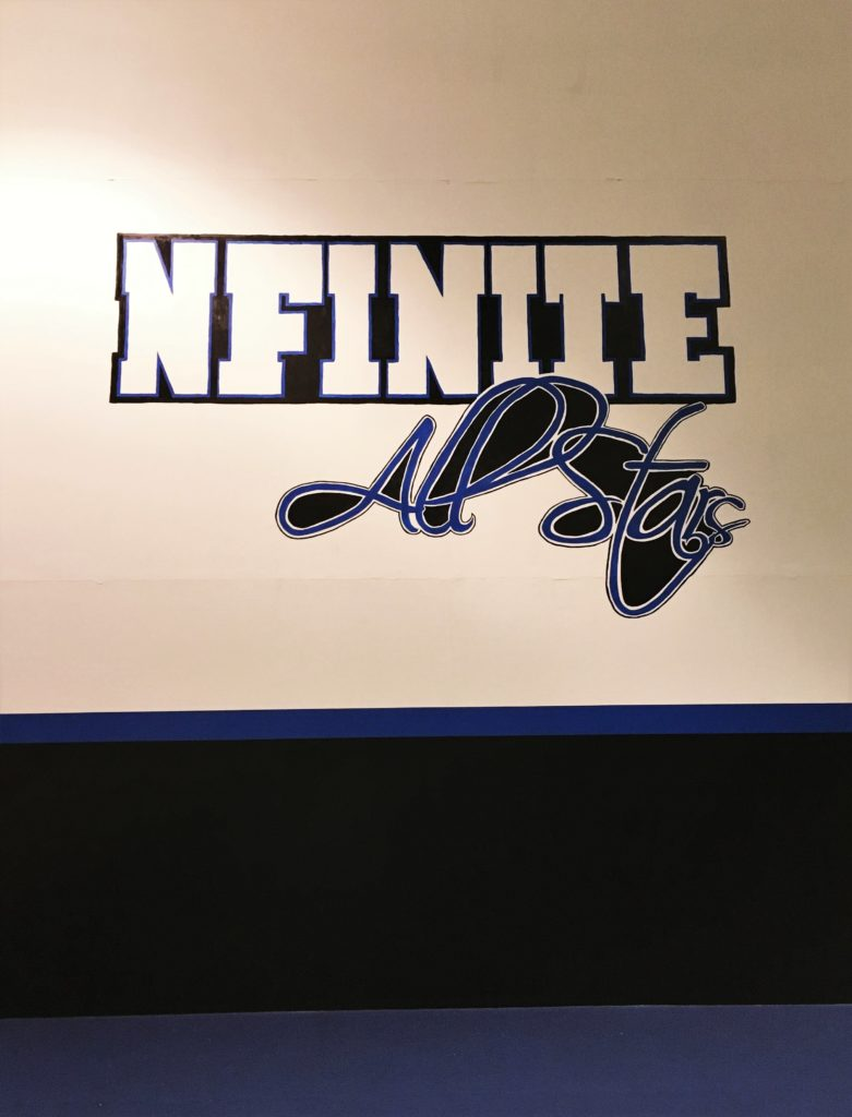 Large hand painted logo on gym wall of cheerleading facility. 10' x 16', 19' high