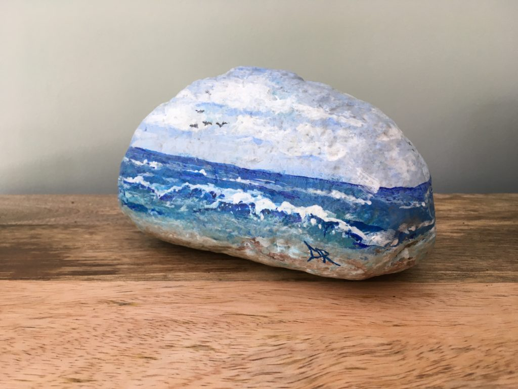 Rock painted with oceanscape scene.