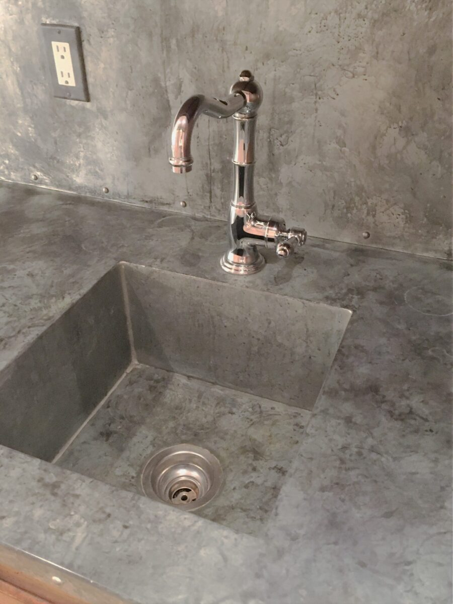 Chemically-induced antique finish on galvanized aluminum sink.