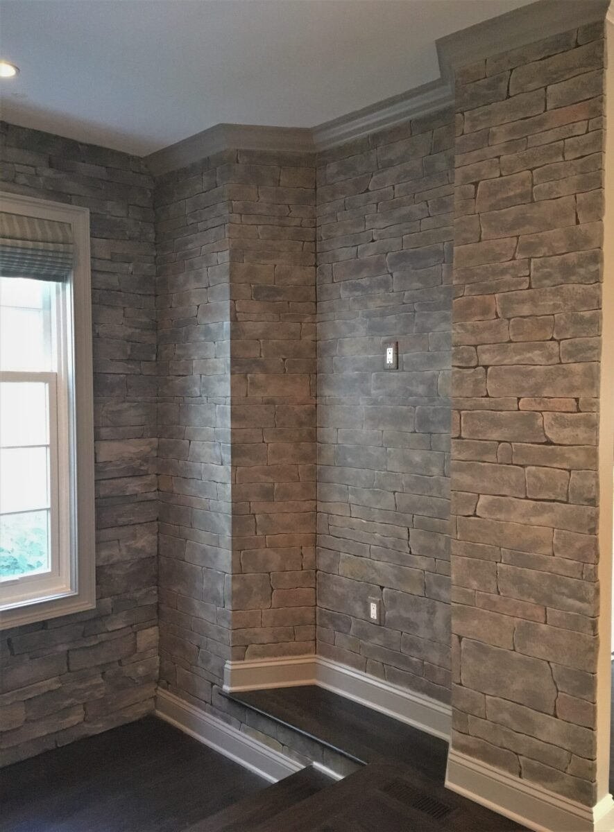Faux stone wall painted adjacent to real stone wall.