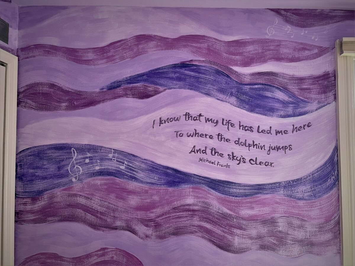 Loose, brushy wave mural in a variety of purples, with song lyric and musical notes.
