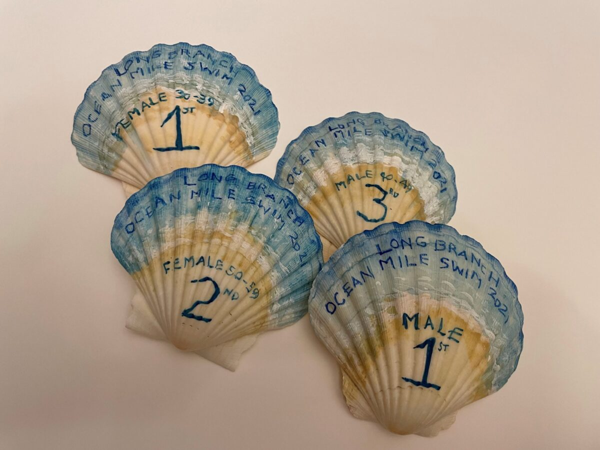 Four of 62 hand painted shells for swim race awards.