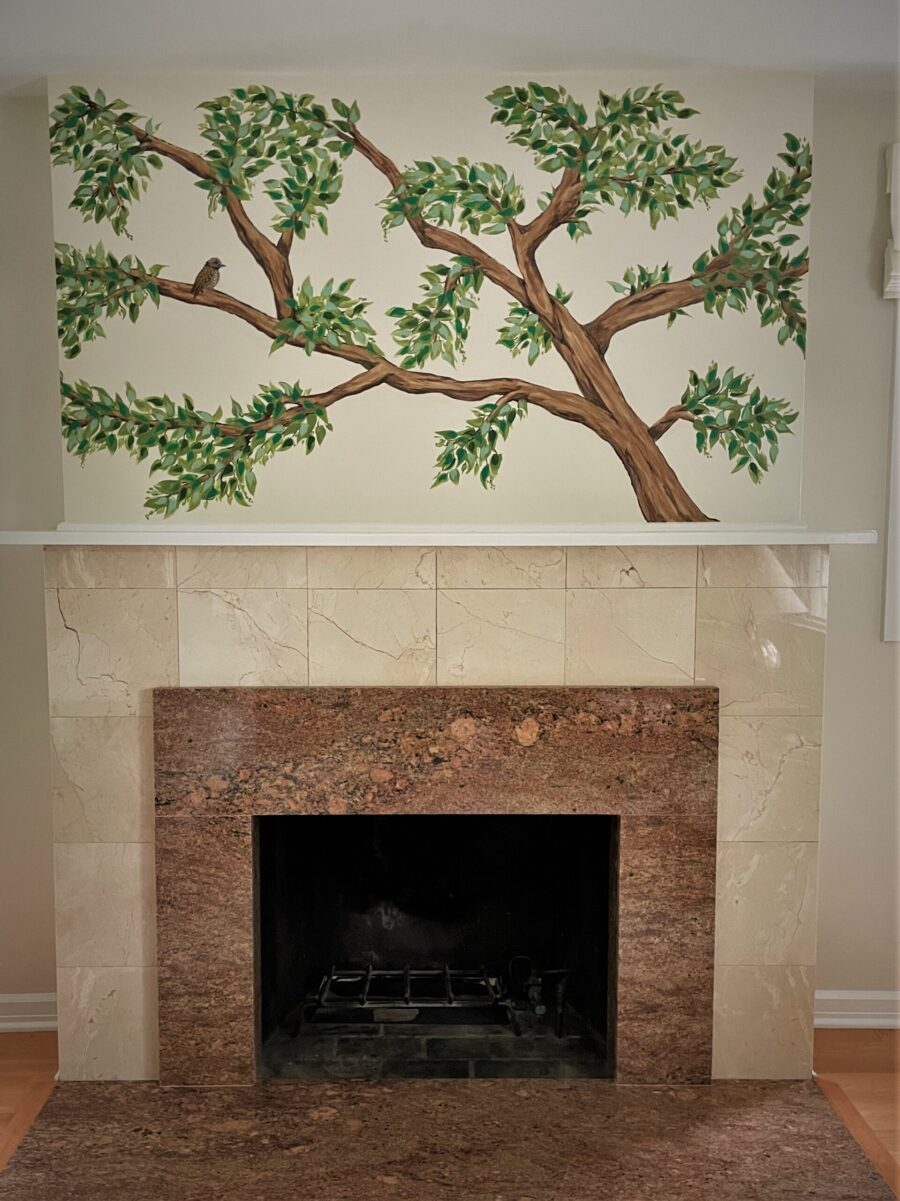 Tree branches with bird painted above fireplace.